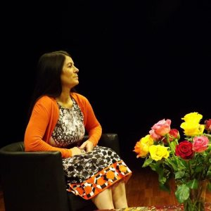 Madeleine sitting in a chair taking part in a speaking event with a vase of colourful flowers in front of her
